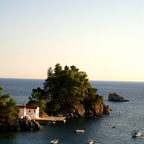 Little chapel on a lush islet. Little boats on the blue sea in Parga, a breathtaking place.
