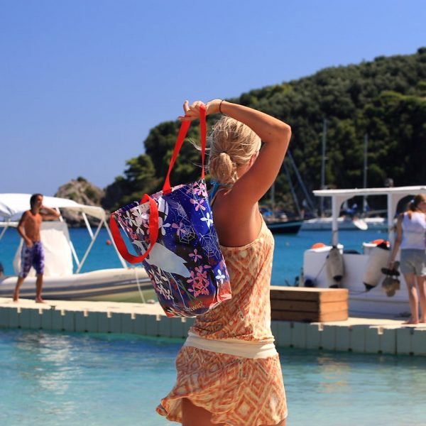 A tourist walking along the port of Parga, where Adams Hotel is located.