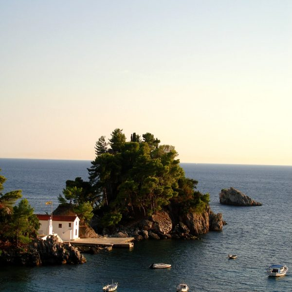 A chapel built by the sea and littles boats floating on the sea in Parga.