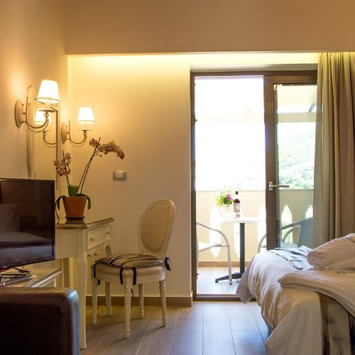 Double bed, TV set, desk and chair by the window at Junior Suite in Parga.